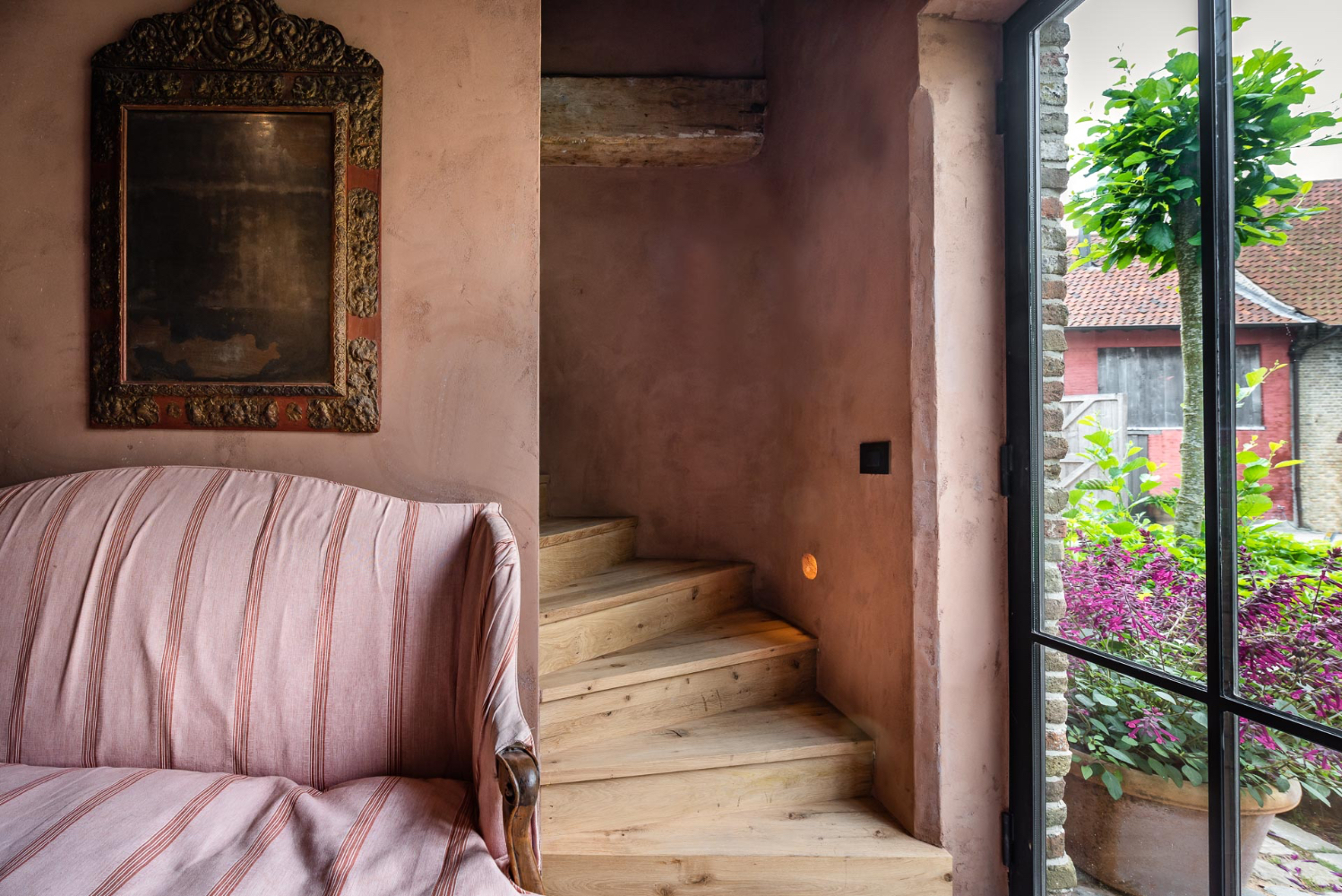Rosy plaster walls, character rich wood steps, and exquisitely decorated interiors grace The Little Monastery, a B&B by Brigitte Garnier. Come see more!