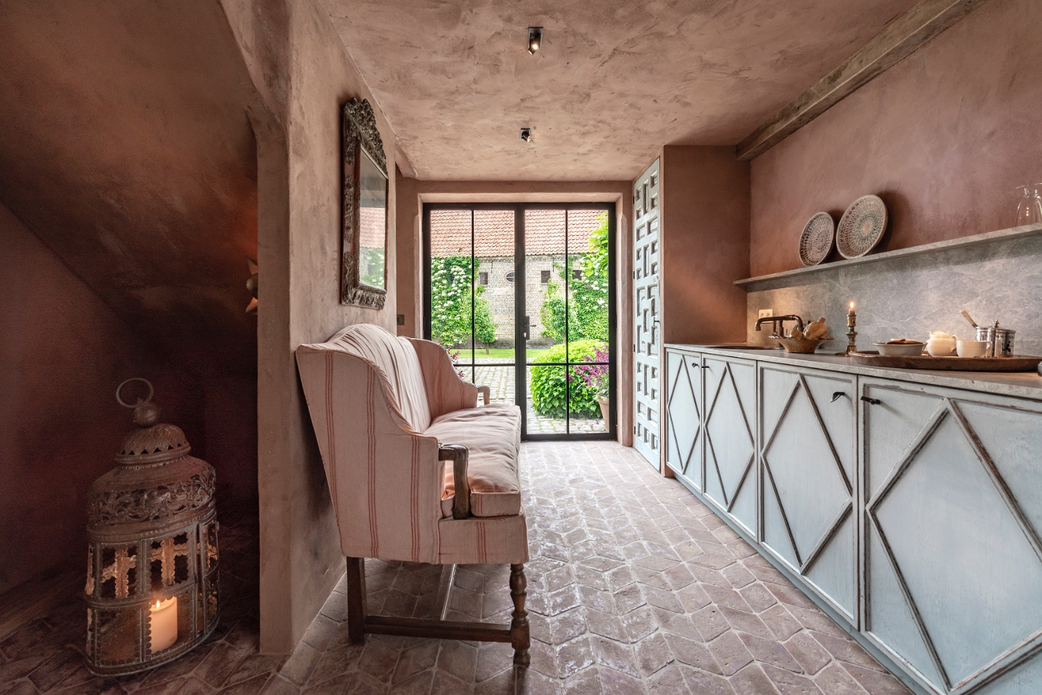 Warm rosy plastered walls and ceiling in a Belgian style interior at The Little Monastery. Come enjoy photos of Old World Style and Rustic European Antiques in a Serene Countryside Setting.