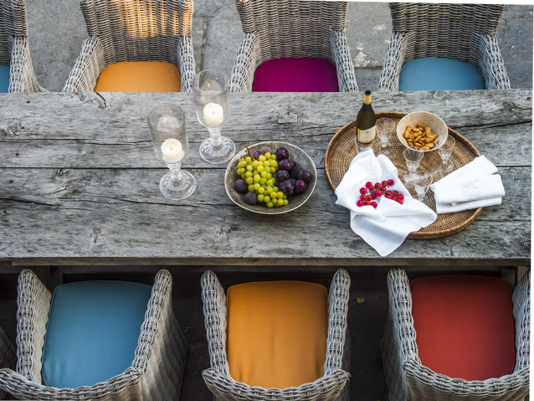 Colorful upholstered cushions and weathered dining table at The Little Monastery, a wonderful B&B near Bruges. Come enjoy photos and a tour of Belgian Design Style Inspiration from antiques dealers Alain and Brigitte Garnier.