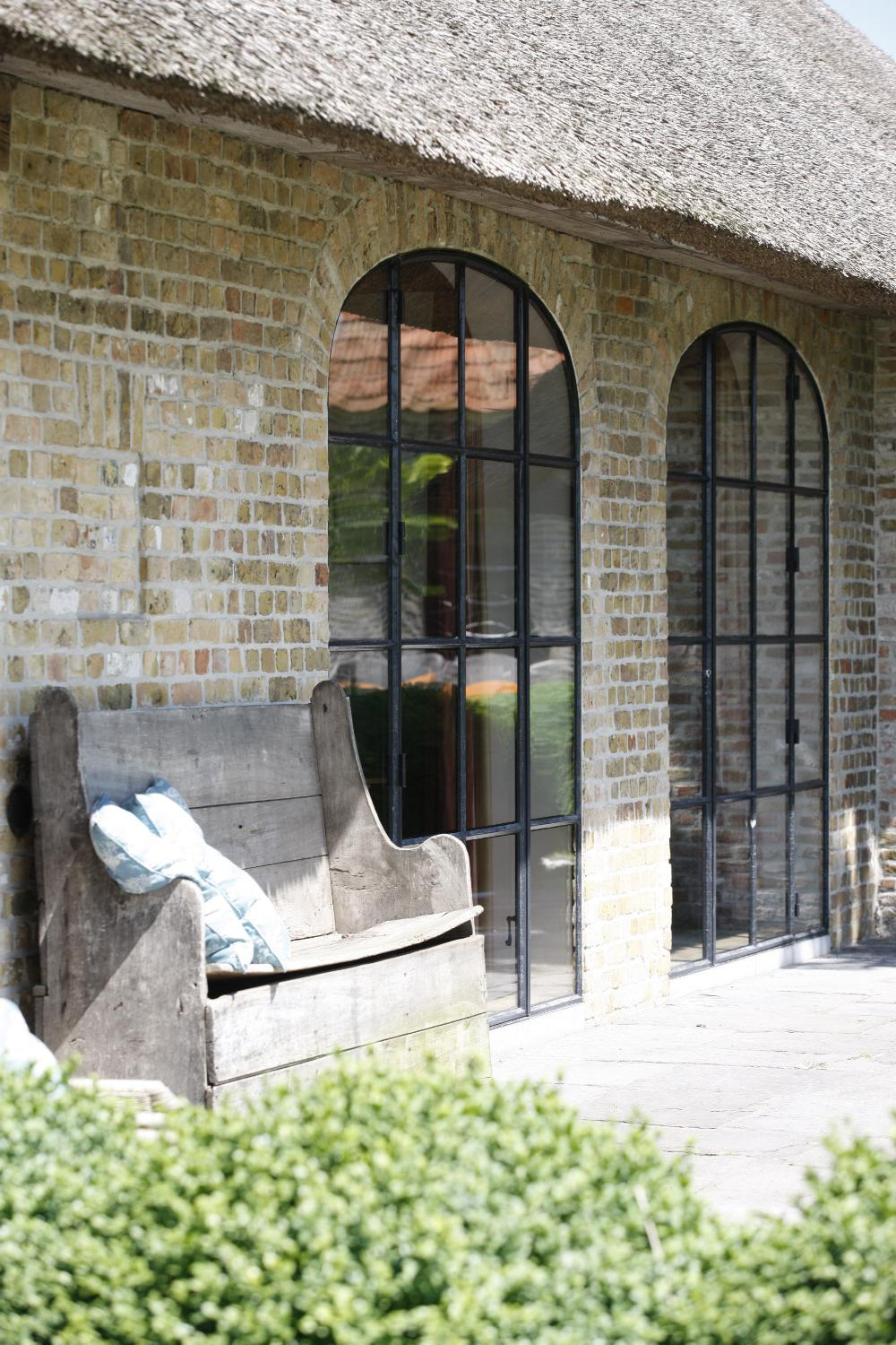 Arched steel and glass doors, old brick, and an ancient wood bench at The Little Monastery, a wonderful B&B near Bruges. Come enjoy photos and a tour of Belgian Design Style Inspiration from antiques dealers Alain and Brigitte Garnier.